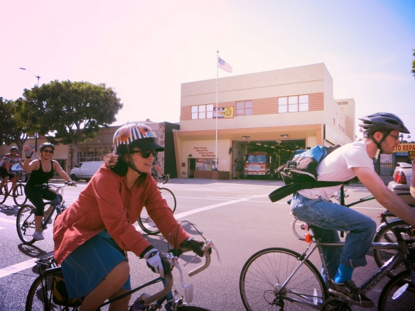 Cyclists ride by Highland Park's Los Angeles Fire Department No. 12 on Figueroa.